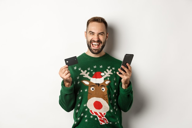 新年、オンラインショッピング、クリスマスのコンセプト。白い背景の上に立って、クレジットカードとスマートフォンを使用して興奮した男
