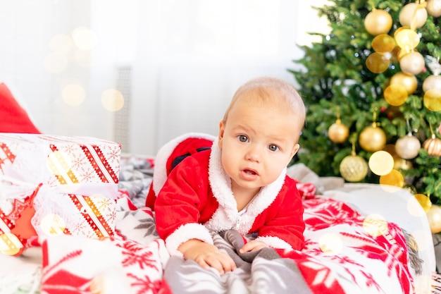 새해나 크리스마스, 산타클로스 의상을 입고 크리스마스 트리에 있는 집에 있는 아기가 웃고 휴가를 기다리고 있다