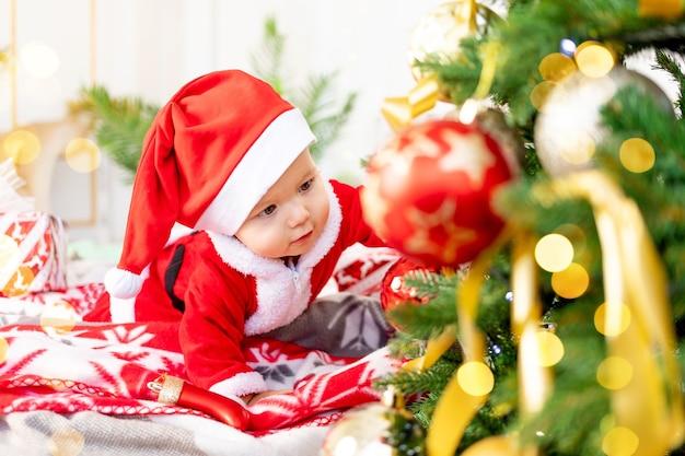 새해나 크리스마스, 산타클로스 의상을 입은 크리스마스 트리 옆에 있는 침대에 누워 있는 아기와 모자를 쓰고 웃고 크리스마스 장난감을 가지고 놀고 웃고 휴가를 기다리는