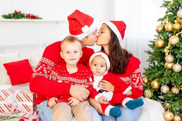 새해나 크리스마스, 크리스마스 트리 옆에 있는 집 침대에 두 아이가 있는 행복한 가족은 크리스마스 트리에서 웃고, 포옹하고, 휴가를 축하하는 키스를 합니다.