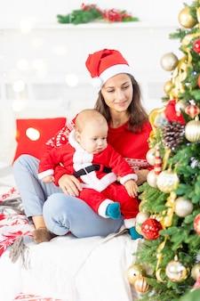 새해 또는 크리스마스, 산타클로스 의상을 입고 크리스마스 트리 옆에 있는 집에서 아기를 안고 껴안고 휴가를 기다리는 젊은 어머니