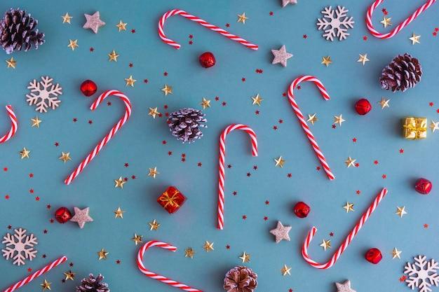 Новый год или рождественский фон. плоские лей из сосновых шишек, рождественских игрушек и леденцов на синем фоне