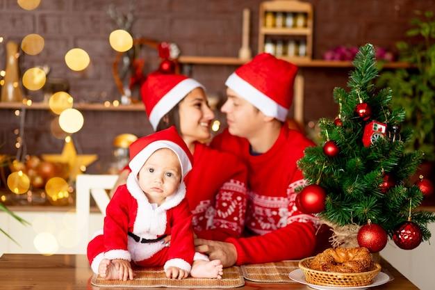 새해 또는 크리스마스, 부엌에 있는 빨간 스웨터와 산타클로스 모자를 쓴 아기의 클로즈업, 행복한 젊은 가족 엄마, 아빠, 그리고 크리스마스 트리에서 웃고 포옹하는 아기