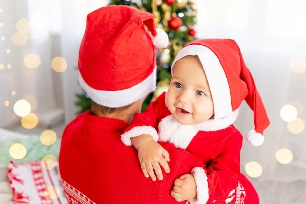 새해나 크리스마스, 산타클로스 의상을 입고 크리스마스 트리에서 집에 있는 아기를 안고 있는 아빠와 모자는 웃고 포옹하고 휴가를 기다리고 있습니다.