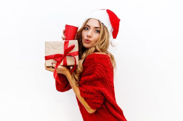 새해 또는 크리스마스 이브 분위기. 선물 상자를 들고 가장 무도회 모자에 금발 매력적인 여자 즐거운 분위기입니다.