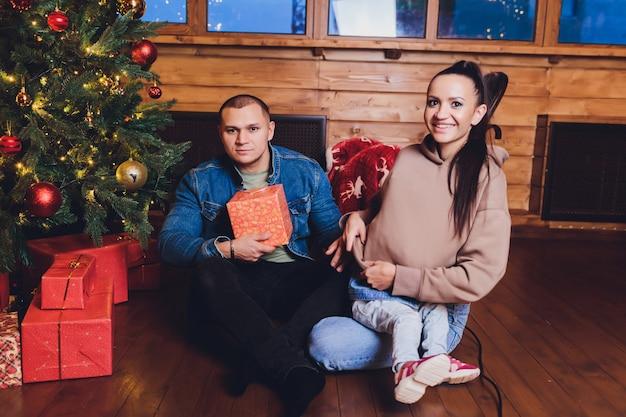 Новый год или рождество, портрет красивой семьи, папы, мамы и дочери возле новогодней елки, рождественский вечер, нежная и счастливая семья зимой, отец держит дочь на руках.