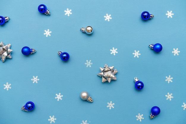 パステルブルーの背景に白と青のボールと雪片の新年または冬の構成パターン...