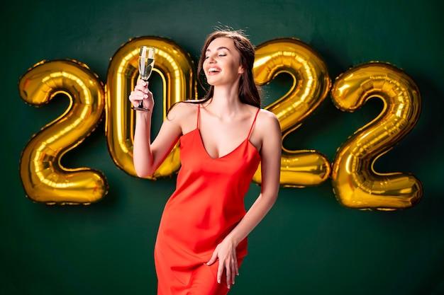 シャンパンと新年会の気球紙吹雪緑の背景の女性を祝う