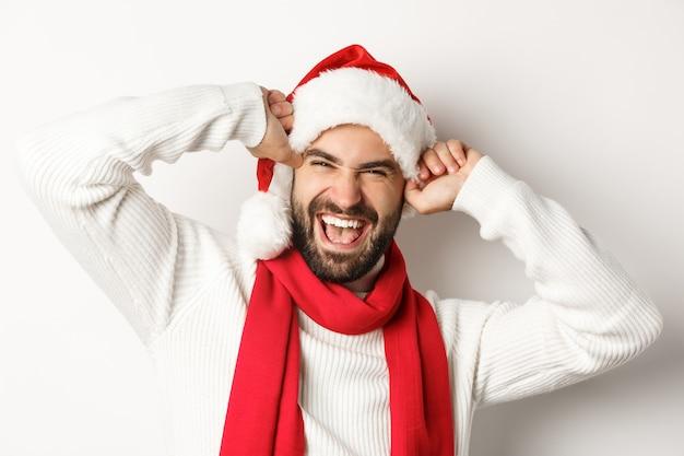 年末年始のパーティーと冬の休日のコンセプト。クリスマスを祝って、笑顔でサンタの帽子、白い背景を身に着けている陽気なひげを生やした男のクローズアップ