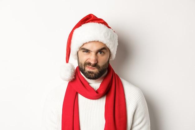 年末年始のパーティーと冬の休日のコンセプト。白い背景に立って、眉をひそめ、顔をゆがめているサンタ帽子の不機嫌そうな男のクローズアップ