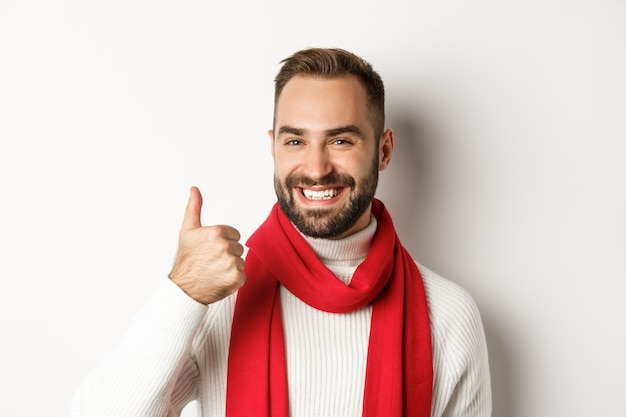 年末年始のパーティーと冬の休日のコンセプト。親指を立てて、幸せなクリスマスを願って、白い背景の上に立っているハンサムな満足の男のクローズアップ。