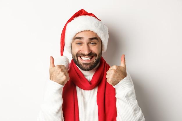年末年始のパーティーと冬の休日のコンセプト。白い背景の上に立って、承認、いいね、同意の親指を示すサンタ帽子の幸せな男のクローズアップ