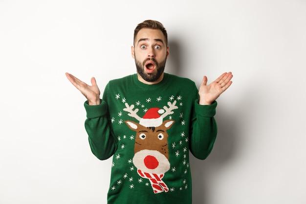 Новогодняя вечеринка и концепция зимних праздников. удивленный бородатый парень, задыхаясь от изумления, стоит в рождественском свитере на белом фоне