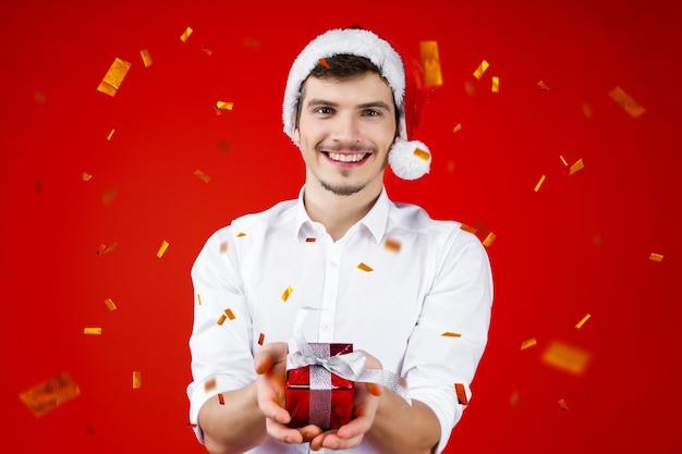 新年パーティーコンセプト幸せな楽しい笑みを浮かべて魅力的なハンサムな流行に敏感な男男男性サンタクロースの帽子を保持している冬クリスマス休暇を祝うプレゼントボックスギフト黄金の紙吹雪