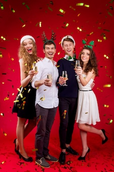 New year party concept happy fun smiling friends company wearing fairy tale carnival costume santa deer christmas tree hat holding glass champagne celebrating winter holidays confetti