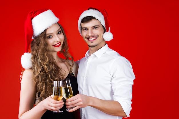 おとぎ話のカーニバルの衣装を着て友人カップルヒップスターを笑顔新年パーティーコンセプト幸せな楽しいサンタクロースクリスマス帽子持株グラスシャンパン乾杯冬の休日を祝う