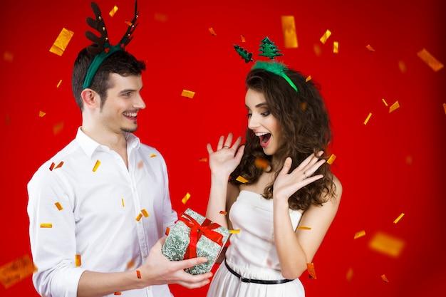 おとぎ話のカーニバル衣装鹿クリスマスツリーの帽子を身に着けている友人カップルを笑って新年パーティーコンセプト幸せな楽しみは、冬の休日を祝うプレゼント驚き分離紙吹雪を与える