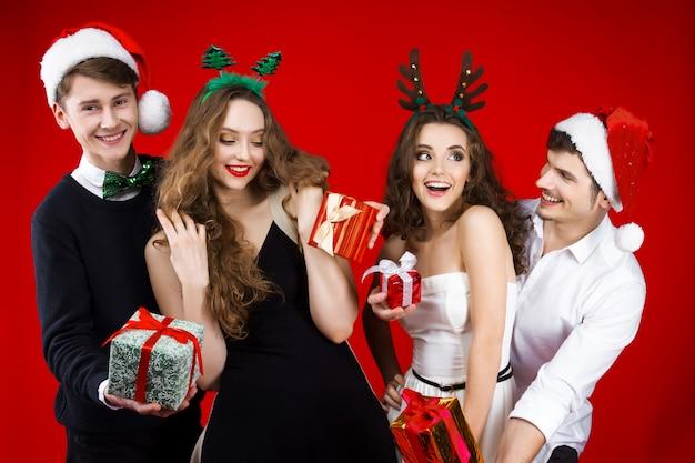 おとぎ話のカーニバルの衣装を身に着けている友人ヒップスター会社を笑って新年パーティーコンセプト幸せ楽しいサンタ鹿クリスマスツリーの帽子は、冬の休日を祝うプレゼントを与える紙吹雪