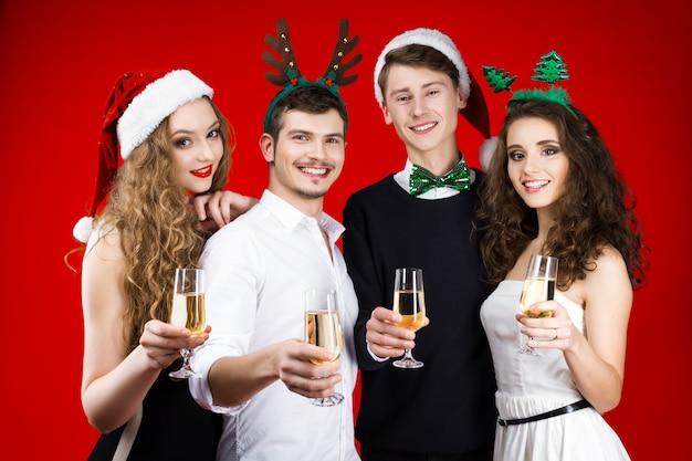 おとぎ話のカーニバルの衣装を身に着けている友人ヒップスター会社を笑って新年パーティーコンセプト幸せ楽しいサンタのクリスマスツリーの帽子を保持している冬の休日を祝うガラスシャンパン
