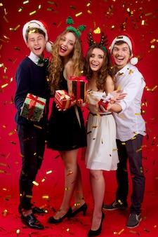Новогодняя вечеринка концепция счастливое веселье улыбающиеся друзья хипстерская компания в сказочном карнавальном наряде санта-олень рождественская елка в шляпе держит подарки празднование зимних праздников конфетти