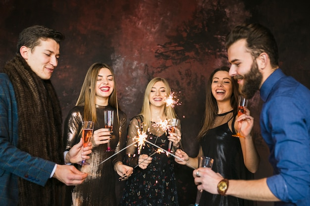 New year party and friendship concept with friends and sparklers