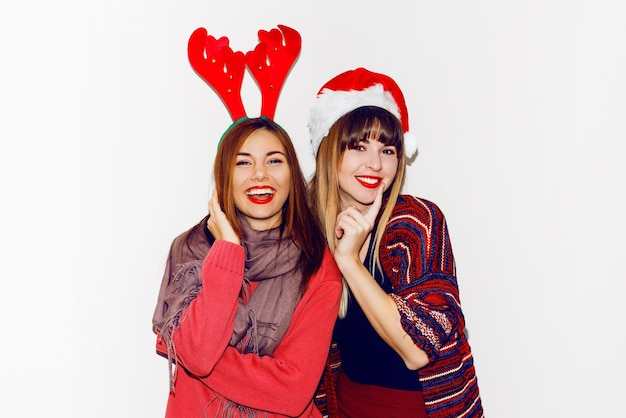 New year party. two beautiful girls in funny masquerade santa's hats send kiss . indoor stockpile image of best friends posing. isolate.