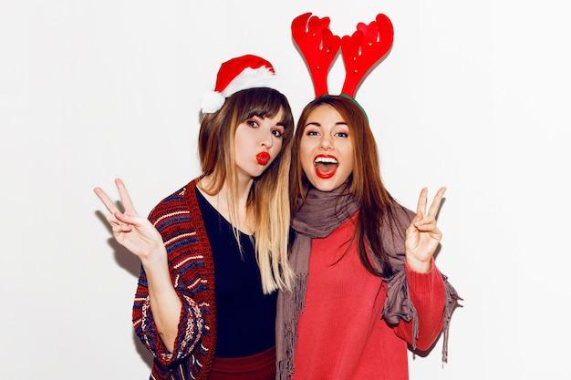 새해 파티. 재미있는 가장 무도회 산타 모자를 쓴 두 명의 아름다운 소녀가 키스를 보냅니다. 가장 친한 친구 포즈의 실내 비축 이미지입니다. 격리.
