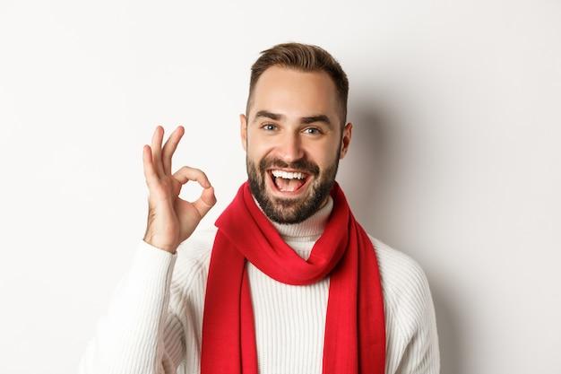 Concetto di festa di capodanno e vacanze invernali. primo piano dell'acquirente maschio soddisfatto che mostra segno ok, approva e accetta, come il prodotto, in piedi su sfondo bianco
