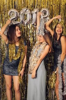Festa di new year con tre ragazze che festeggiano