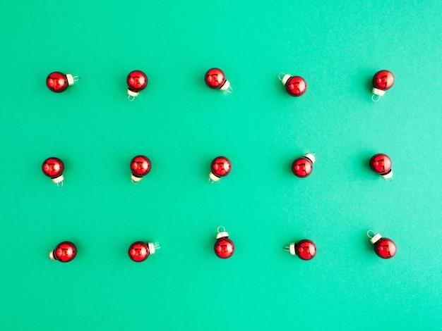新年のパターン、レイアウト、フラットレイ。たくさんの赤いクリスマスツリーのおもちゃが緑の背景にあります。