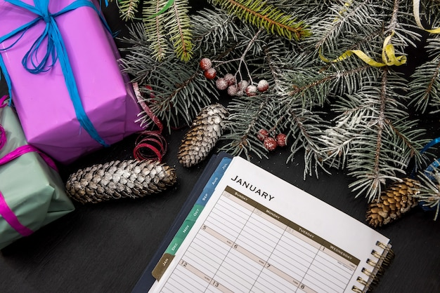 New year planning concept. fir branches with colorful gift boxes on dark background