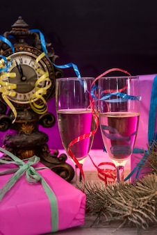 New year postcard with champagne glasses, colorful packages and clock