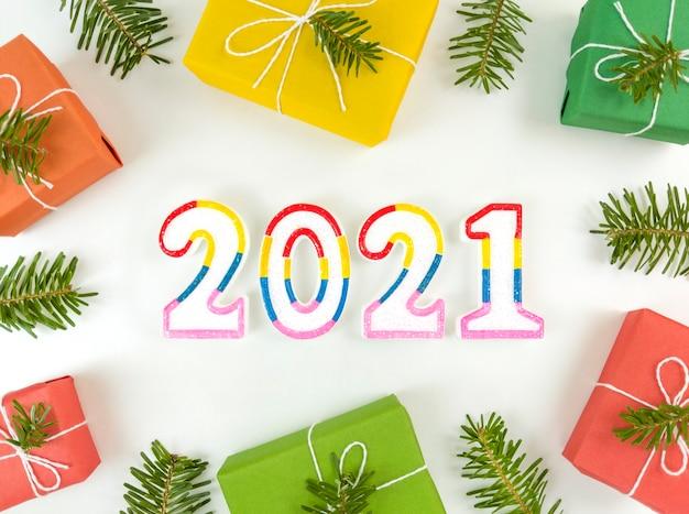 Новогодняя открытка с еловыми ветками, подарочными коробками и фигурами 2021 года на белом фоне.