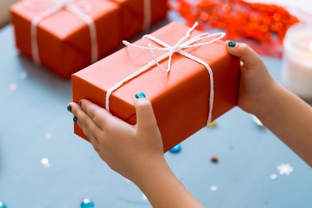 새 해가 빨간색 종이 포장에 있습니다. 선물 상자를 들고 손. 인사말 놀라움과 보상 개념.