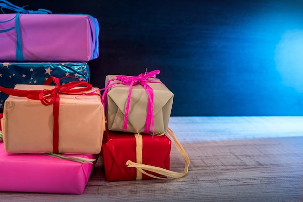 New year presents. colorful gift boxes on wooden table against dark wall