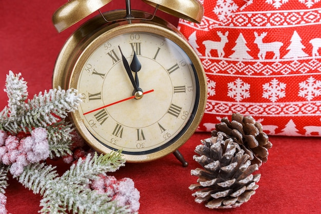 New year red background with snow fir christmas tree, alarm clock and gift bag. the red clock counts down to twelve.