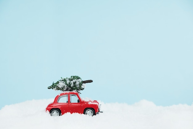 New year red car with christmas tree in a snowy landscape