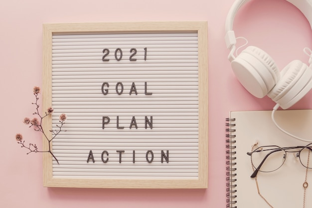 New year resolution. goal plan and action on letter board with notepad and headphone