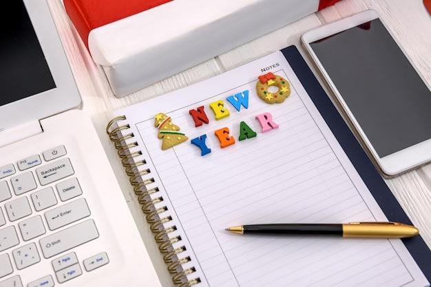 Новогоднее разрешение в блокноте с ноутбуком на столе