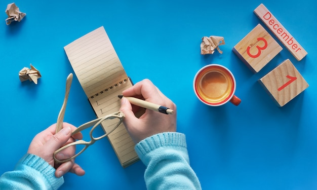 New year resolutions concept, hand with coffee, notebook, wooden calendar and coffee on blue