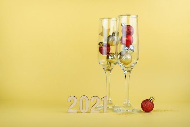노란색 배경에 빈 샴페인 잔과 함께 새해 2021 구성