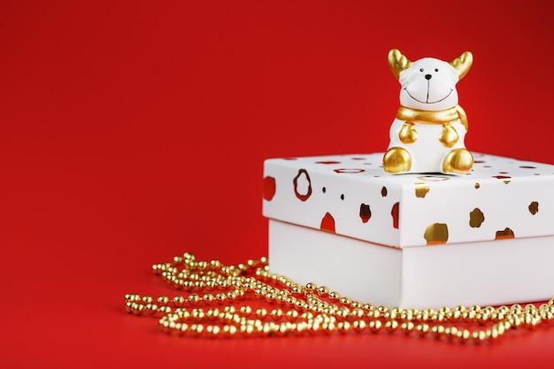 빨간색 배경에 선물을 가진 새 해의 2021 장난감 황소.