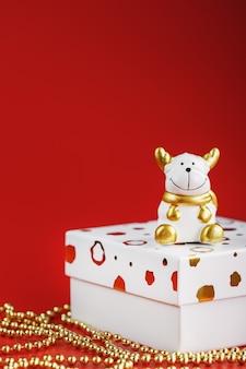 Новогодний игрушечный бык 2021 года с подарком на красном фоне.