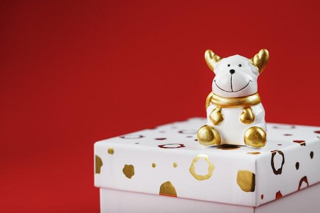 빨간 벽에 선물을 가진 새해 2021 장난감 황소. 선물 상자와 금 구슬. 새해와 휴일의 상징. 공간을 복사하십시오.