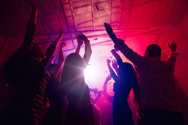 新年。シルエットの人々の群衆は、ネオンの光の背景のダンスフロアに手を上げます。ナイトライフ、クラブ、音楽、ダンス、モーション、若者。パープルピンクの色と感動的な女の子と男の子。