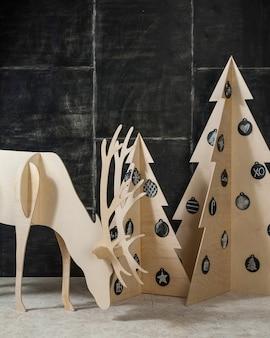新年とクリスマスの装飾とモミ合板の鹿と暗い背景の木