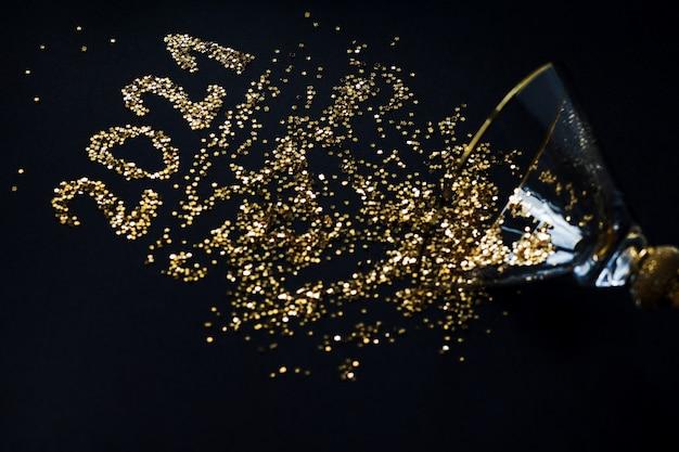 正月とクリスマス。黒い背景に光沢のあるガラスから散らばったスパンコールからの番号2021。