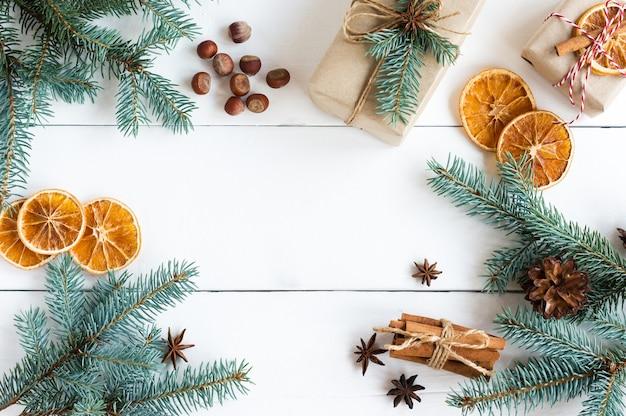 Новогодний фон с еловыми ветками, орехами, палочками корицы, дольками апельсина, праздничными коробками. копия пространства.