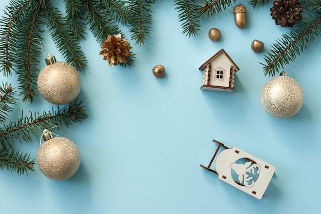 은색 공, 견과류, 나무 장난감, 가문비나무 가지가 있는 새해 파란색 배경. 평면 레이아웃. 평면도.
