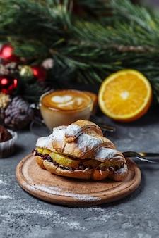 Новогодний завтрак с круассанами. новогодний круассан с шоколадом и печеным апельсином